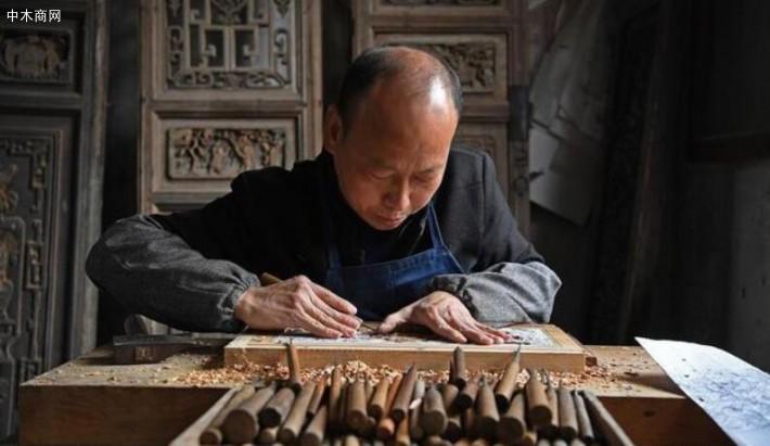 """俞友鸿在雕刻""""三英战吕布""""题材的木雕作品"""